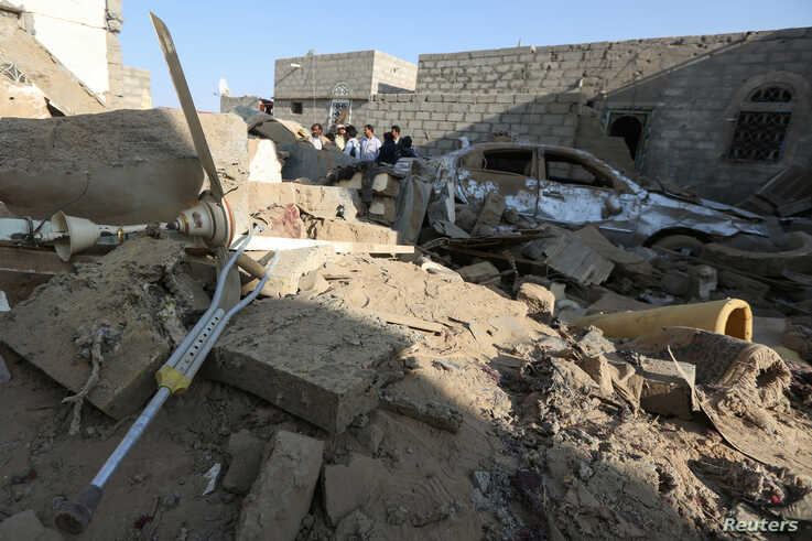 People stand at the site of a Houthi ballistic missile attack over the populated district of Rawda in Marib, Yemen, Febr. 6, 2020.