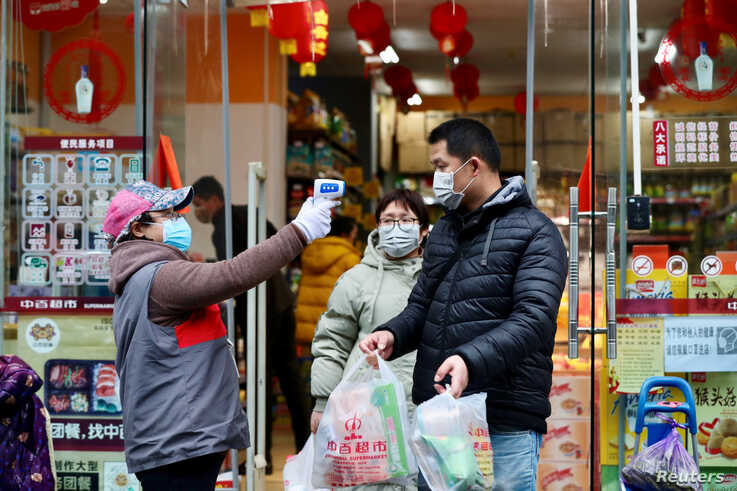 A worker measures body temperature of people leaving a supermarket in Qingshan district following an outbreak of the novel…