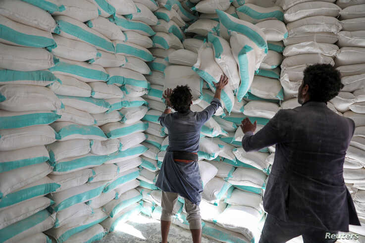 Workers handle sacks of wheat flour at a World Food Programme food aid distribution center in Sanaa, Yemen February 11, 2020…