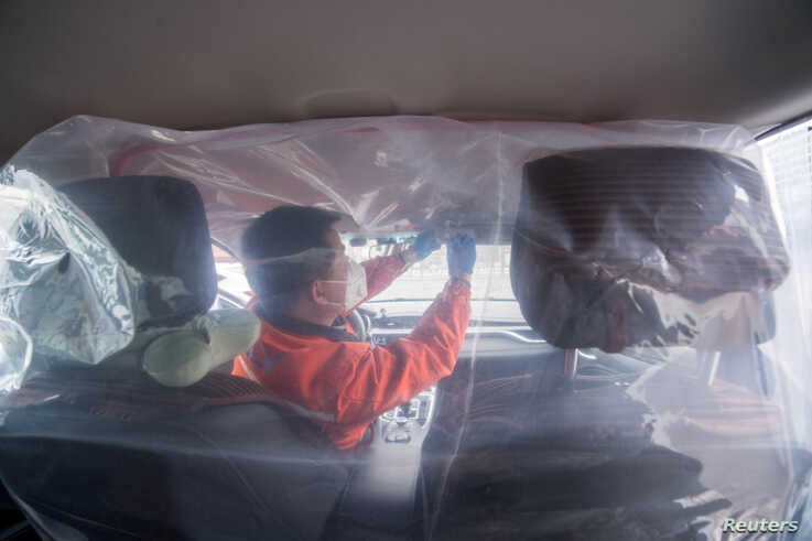 A worker installs plastic film to separate the front seats from the back, inside a vehicle for a car-hailing service as the…
