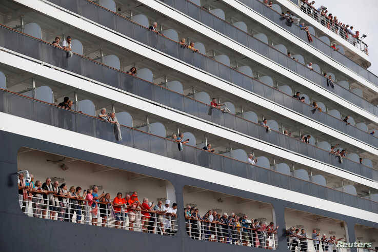 Passengers wave their towels as they are about to leave MS Westerdam, a cruise ship that spent two weeks at sea after being…