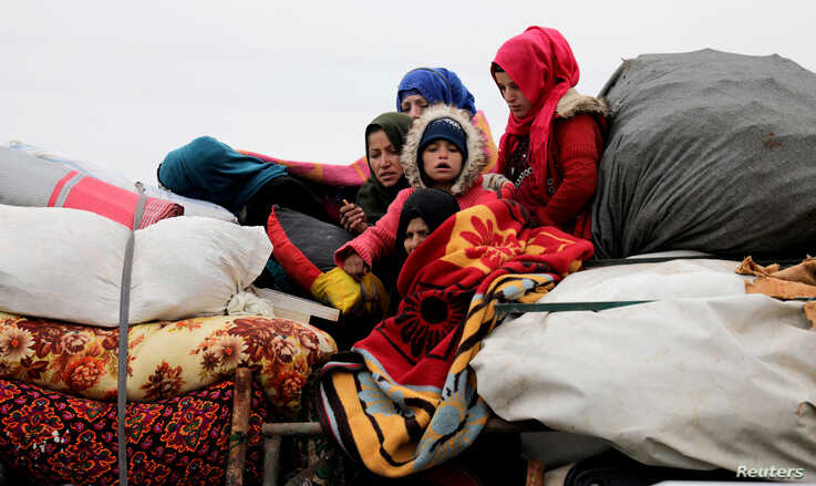 FILE PHOTO: Internally displaced Syrians from western Aleppo countryside, ride on a vehicle with belongings in Hazano near…