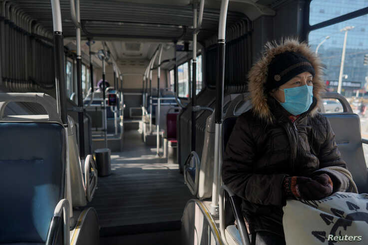 A woman wearing a face mask sits inside a public bus, as the country is hit by an outbreak of the novel coronavirus, in Beijing…
