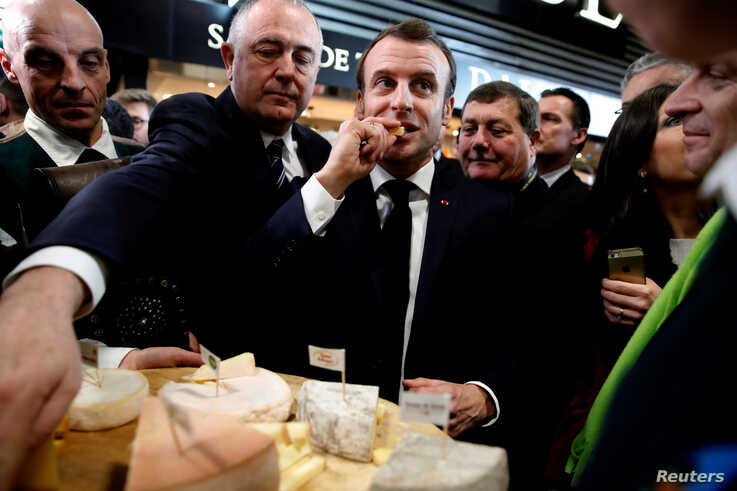 French President Emmanuel Macron eats cheese during a visit to the 57th International Agriculture Fair (Salon international de…