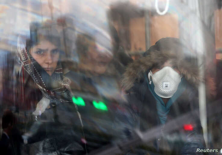 An Iranian woman wears a protective masks to prevent contracting coronavirus, as she sits in the bus in Tehran, Iran February…