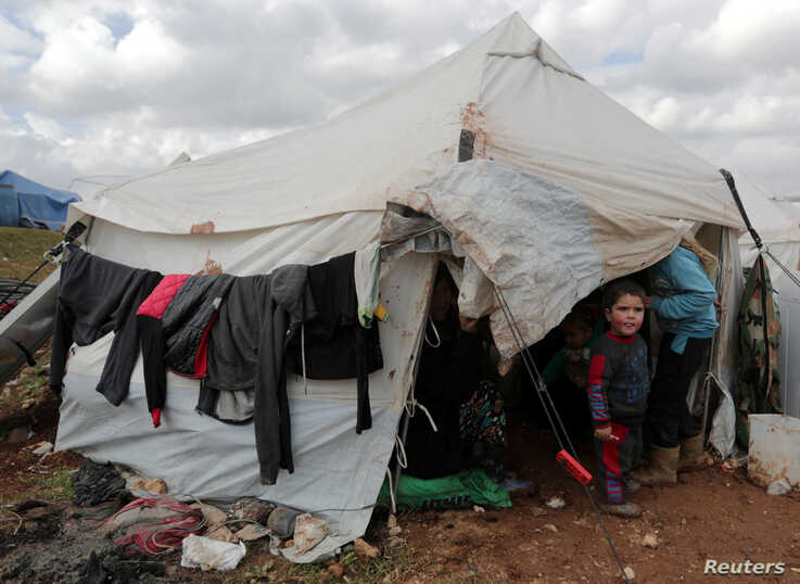 An internally displaced Syrian child from Idlib, stands outside a tent in Azaz, Syria February 22, 2020. Picture taken February…