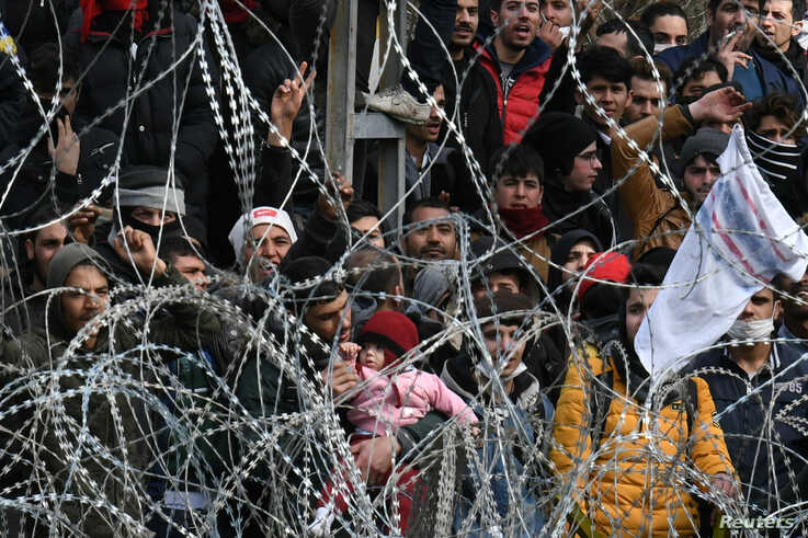 Migrants who want to cross into Greece from Turkey's Pazarkule border crossing shout slogans as they are gathered at the…