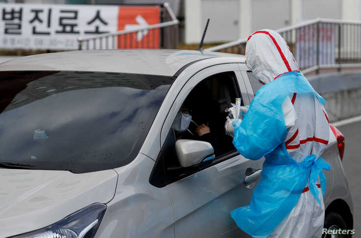 A medical staff member in protective gear prepares to take samples from a visitor at a 'drive-thru' testing center for the…