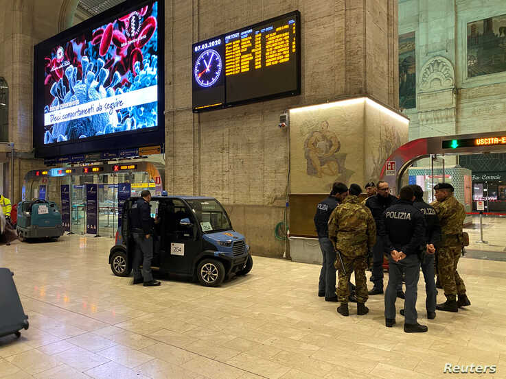 Military and policemen are seen inside Milan's main train station as Italian authorities prepare to lock down Lombardy to…