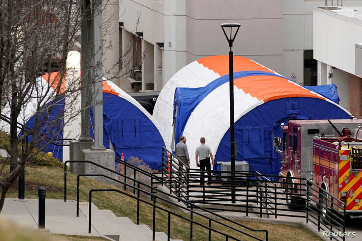 Officials from hospital support services talk outside newly erected negative pressure screening tents that are set up outside…