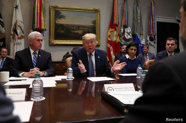 U.S. President Donald Trump speaks next to Vice President Mike Pence during a coronavirus briefing with health insurers in the…