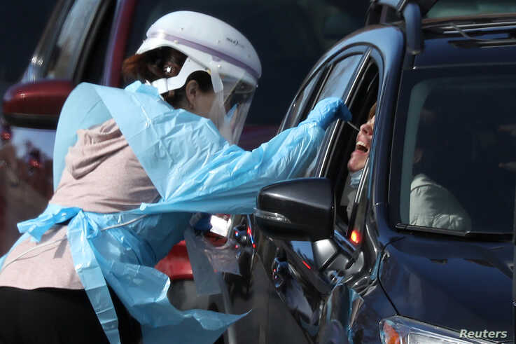 Health care worker tests people at a drive-thru testing station run by the state health department, for people who suspect they…