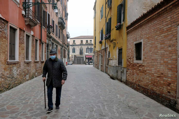 FILE PHOTO: An elderly man with a protective mask walks in Venice, on the fourth day of an unprecedented lockdown across all…