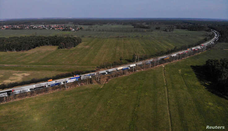 FILE PHOTO: Trucks wait before the German-Polish border checkpoint Forst, as the two countries try to contain the spread of…