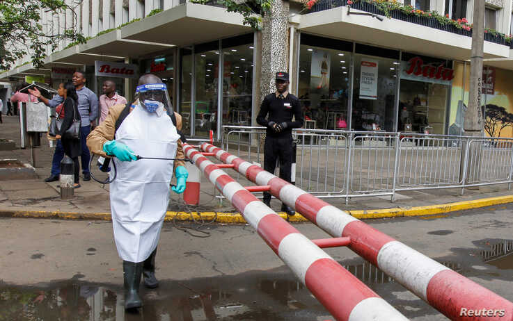A worker sprays disinfectant on a security barrier outside a hotel to prevent the spread of coronavirus disease (COVID-19)…