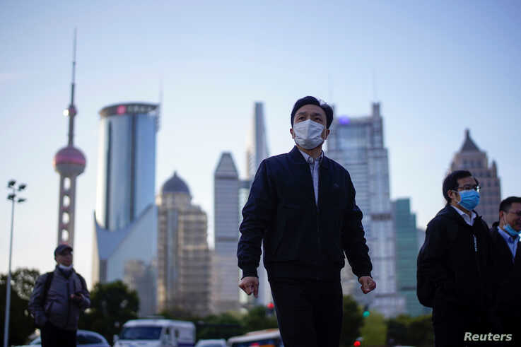 People wear protective face masks, following an outbreak of the novel coronavirus disease (COVID-19), at Lujiazui financial…