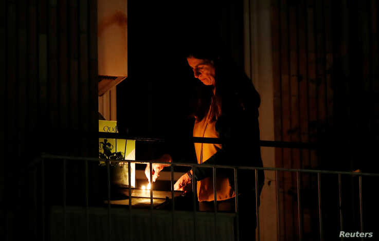 A woman lights a candle on her balcony as faithful across Italy say a prayer for people suffering from coronavirus disease …