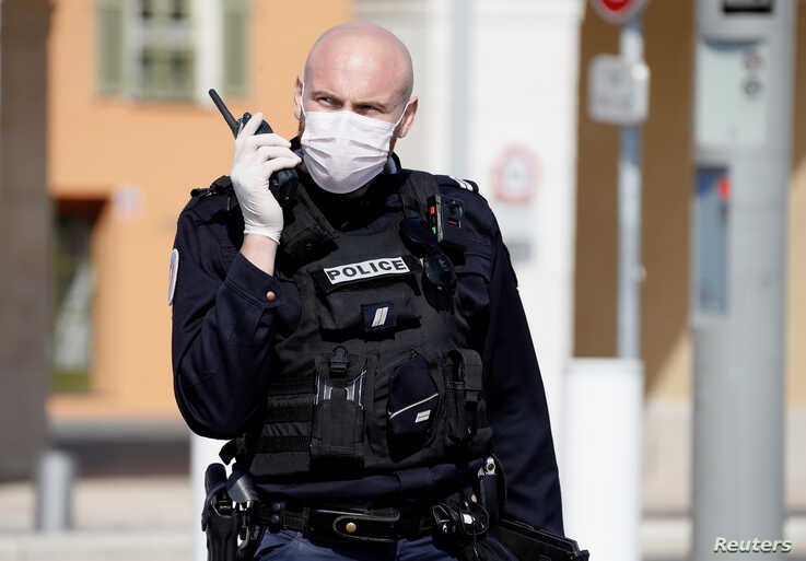 A police officer wearing a protective face mask patrols on the Promenade des Anglais in Nice, as Nice's mayor said on Friday he…