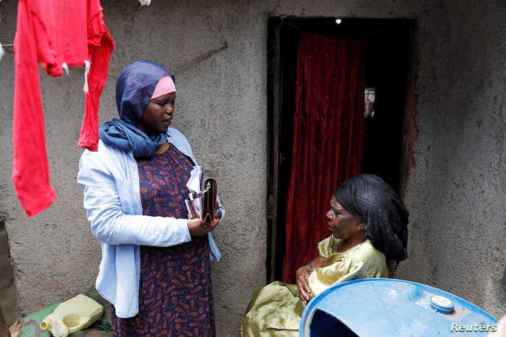 Fatima Juma (R) receives information on how to prevent the spread of the coronavirus disease (COVID-19) from a volunteer of the…