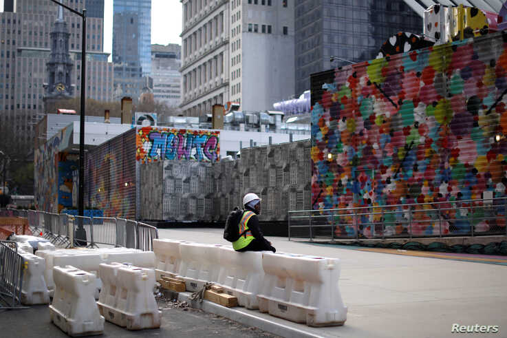 A construction worker sits alone along an empty sidewalk near the World Trade Center in lower Manhattan during the outbreak of…