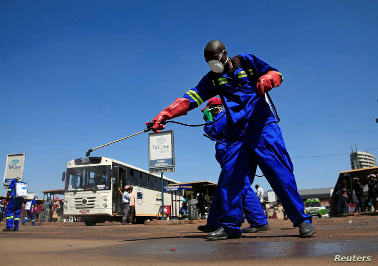 City health workers spray disinfectant at a bus terminus during a 21 day nationwide lockdown to limit the spread of coronavirus…