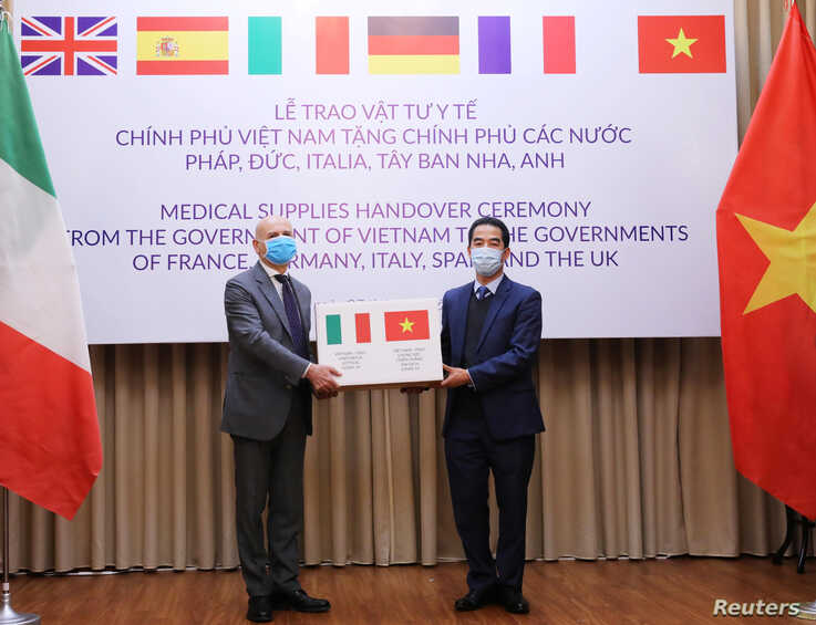 Vietnam's Deputy Foreign Minister To Anh Dung hands a box of protective masks to Italy's Ambassador to Vietnam Antonio…