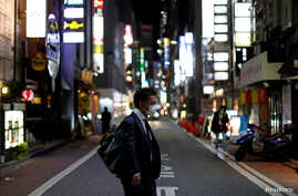 A man wearing a protective face mask, following an outbreak of the coronavirus disease (COVID-19), walks at Ginza shopping and…