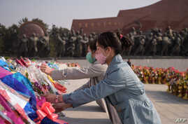 People wearing face masks lay flowers before the statues of late North Korean leaders Kim Il Sung and Kim Jong Il on the…