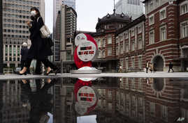 A countdown clock for the Tokyo 2020 Olympics is reflected in a puddle of water outside Tokyo Station in Tokyo, Monday, March…