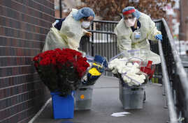 Emergency room nurses transport buckets of donated flowers up a ramp outside Elmhurst Hospital Center's emergency room,…