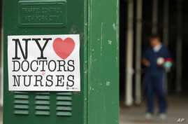 A sign acknowledging the work of doctors and nurses is posted on a traffic control box outside Brooklyn Hospital Center, as a…