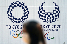 A woman wearing a protective face mask walks near the Tokyo 2020 Olympic and Paralympic Games Thursday, April 2, 2020, in Tokyo…
