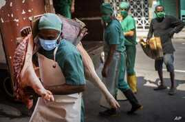 Workers wearing masks as a precaution against the spread of the new coronavirus deliver meat to stores in Havana, Cuba,…