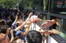 North Koreans on a bus hold hands of their South Korean relatives to bid farewell after the Separated Family Reunion Meeting at…