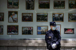 A Chinese policeman wears a face mask as he stands in front of a display of photos of North Korean leaders outside the North…