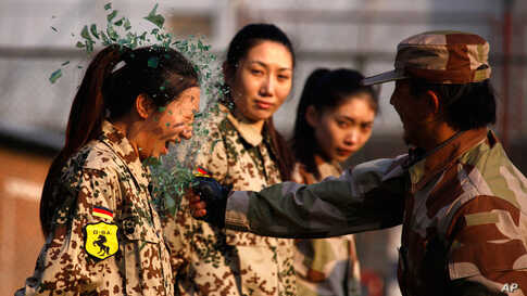 An instructor from the Tianjiao Special Guard smashes a bottle during a training session for China's first female bodyguards in Beijing January 13, 2012. (Reuters)
