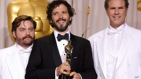 """Bret McKenzie, center, with presenters Zach Galifianakis and Will Ferrell, and his award for best original song for """"Man or Muppet."""" (AP)"""