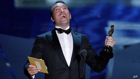 """French actor Jean Dujardin accepts the Oscar for Best Actor for his role in the film """"The Artist"""" at the 84th Academy Awards in Hollywood, California, February 26, 2012. (Reuters)"""