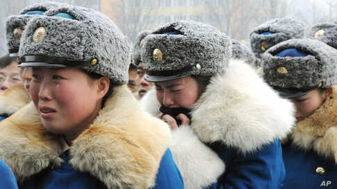 North Korean traffic control women react to the news of Kim Jong-il's death in Pyongyang, December 21, 2011. (Reuters/Kyodo)