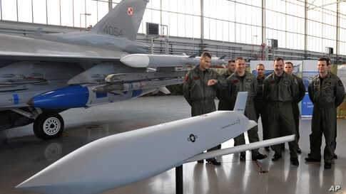 A group of Polish Air Force pilots stand next to a F-16 fighter jet and a model of a JASSM missile as they attend a contract…