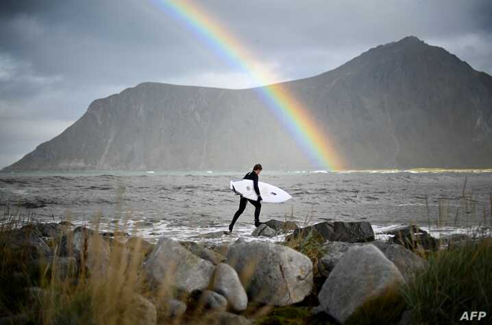 Surfer Anker Olsen Frantzen, 17, of Norway, walks to the water for a free surf session on September 26, 2018,  in Flackstad, Northern Norway, the eve of the Lofoten Masters 2018.