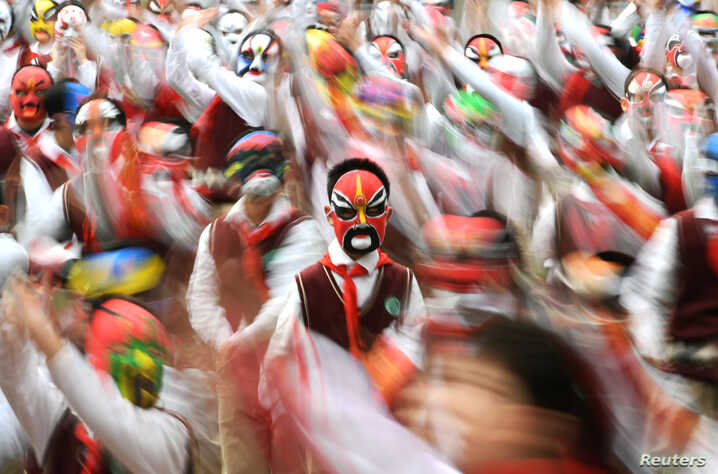 Students wearing traditional opera masks attend an exercise session in Wuhan, Hubei province, China.