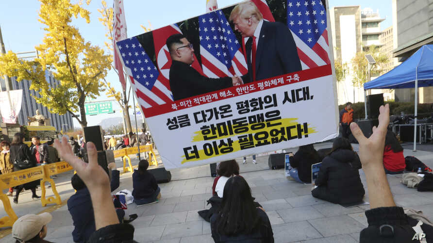 FILE - A protester tosses a banner showing a photo of U.S. President Donald Trump and North Korean leader Kim Jong Un during a rally against the United States' policy to put steady pressure on North Korea near the U.S. Embassy in Seoul, South Korea, No...