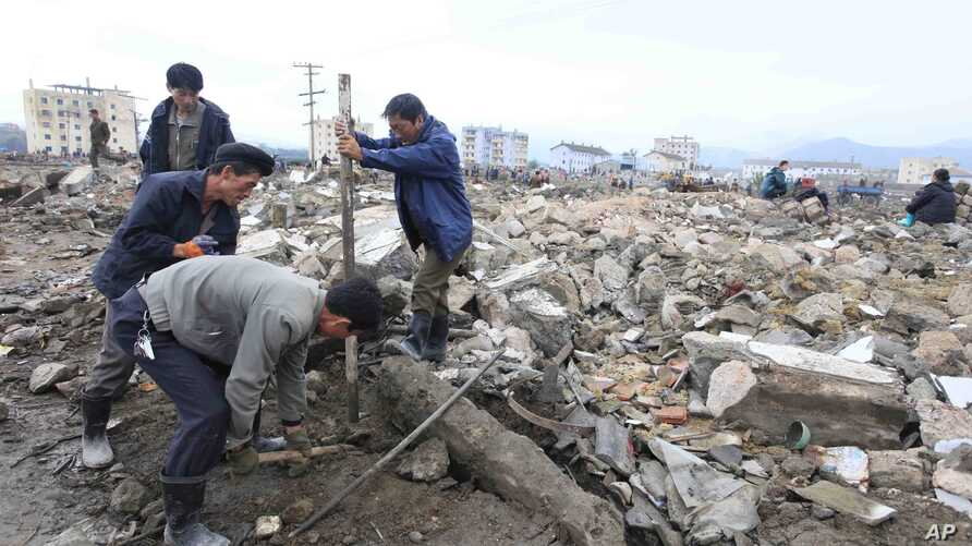 Workers recover cement blocks from flood-damaged areas in Onsong, North Korea, Sept. 16, 2016.