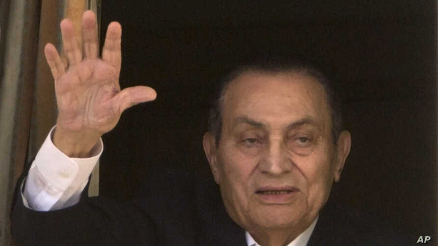 Ousted former Egyptian President Hosni Mubarak waves to his supporters from his room at the Maadi Military Hospital, where he…