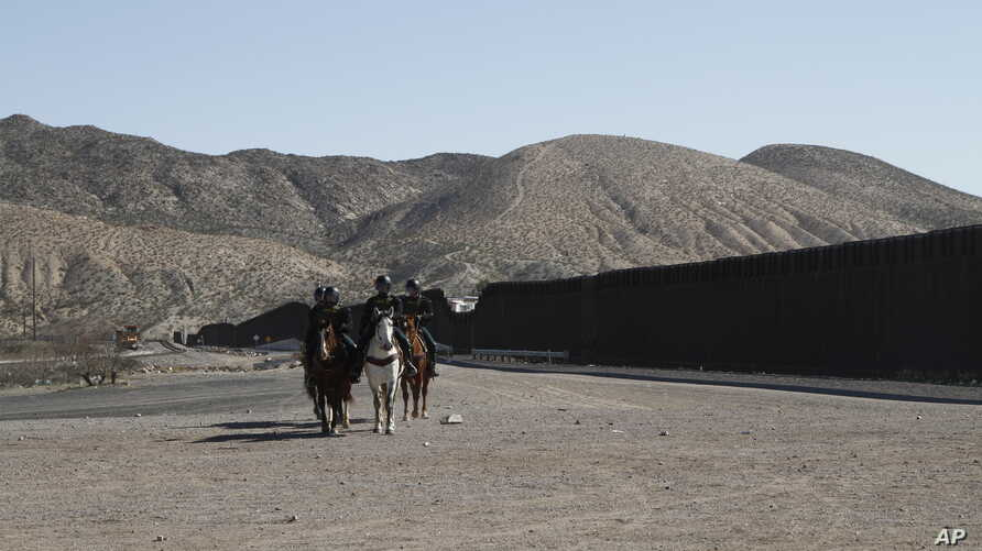 Border Patrol agents on horseback ride away from a US-Mexico border fence on Friday, Jan. 31, 2020, in nearby town of Sunland…