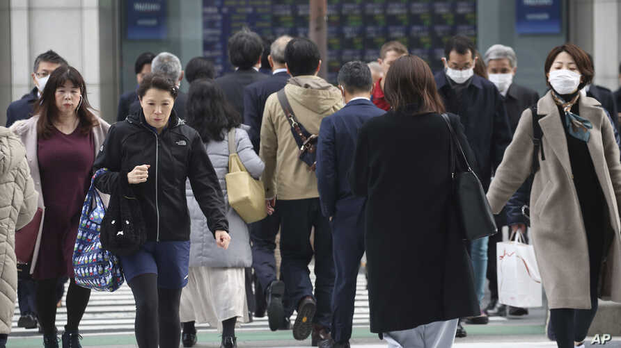 People walk on street in Tokyo, Monday, Feb. 17, 2020. The Japanese economy shrank at an annual pace of 6.3% in the October…