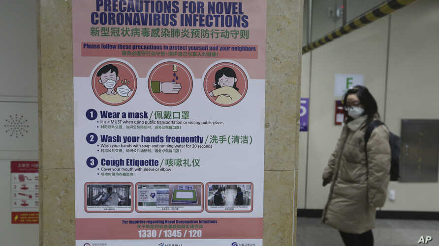 A woman passes by a poster about precautions against a new coronavirus at a subway station in Seoul, South Korea, Thursday, Feb…