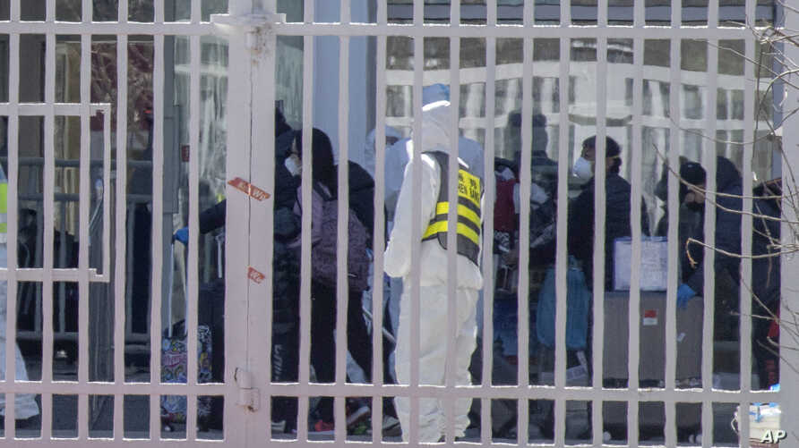 A worker wearing protective overalls watches as oversea passengers arriving from the airport enter an exhibition center…