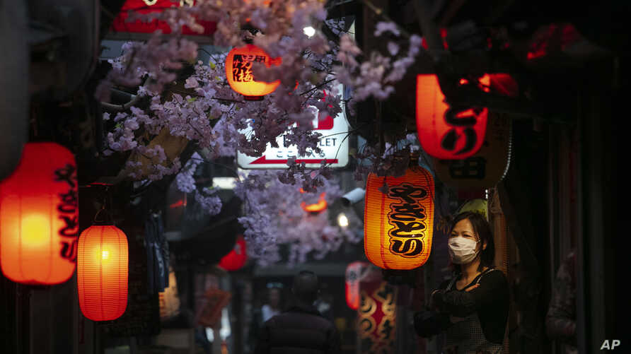 A cook wearing a mask stands outside a restaurant Thursday, March 26, 2020, in Tokyo. Japan's Prime Minister Shinzo Abe is…